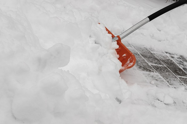 using shovel to remove snow from sidewalk in NYC